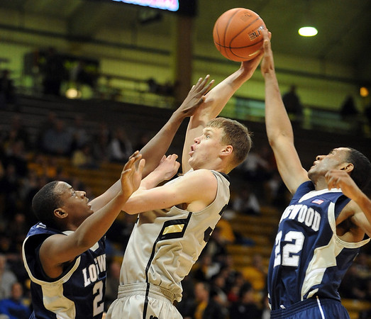 Ben Mills, center, of Colorado, tries to get a shot off between Antwan Carter, left, and Jeylani Dublin, both of Longwood, during the first half of the December 19, 2010 game in Boulder.<br /> Cliff Grassmick / December 19, 2010