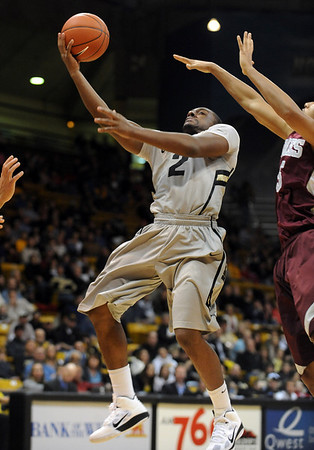 """Shannon Sharpe of Colorado drives past Louis Bell of Maryland Eastern Shore.<br /> For more photos of the game, go to  <a href=""""http://www.dailycamera.com"""">http://www.dailycamera.com</a>.<br /> Cliff Grassmick / December 29, 2010"""