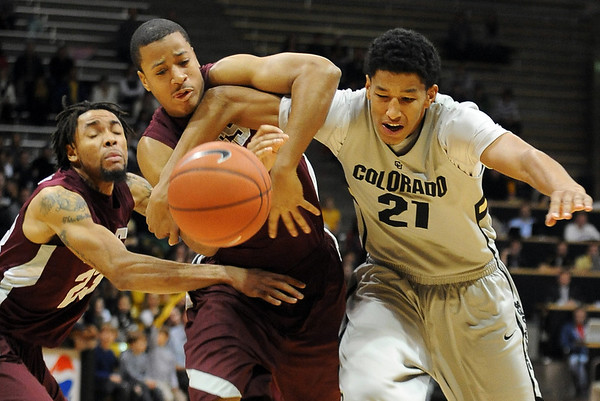 Louis Bell, left, of Maryland Eastern Shore, struggles for a loose ball with Andre Roberson of Colorado, during the first half of the December 29th, 2010 game in Boulder. Dishawn Bradshaw (23) of Maryland ES is in the background.<br /> Cliff Grassmick / December 29, 2010