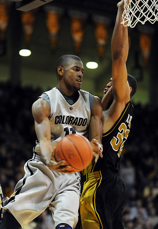Cory Higgins of Colorado, flips a pass around Steve Moore of Missouri during the first half of the February 6, 2010 game in Boulder.<br /> Cliff Grassmick / February 6, 2010
