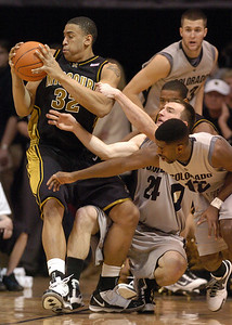 Steve Moore (32) of the University of Missouri, spins away from Levi Knutson (24) and Dwight Thorne, both of Colorado, during the first half of the February 6, 2010 game in Boulder. Cliff Grassmick / February 6, 2010