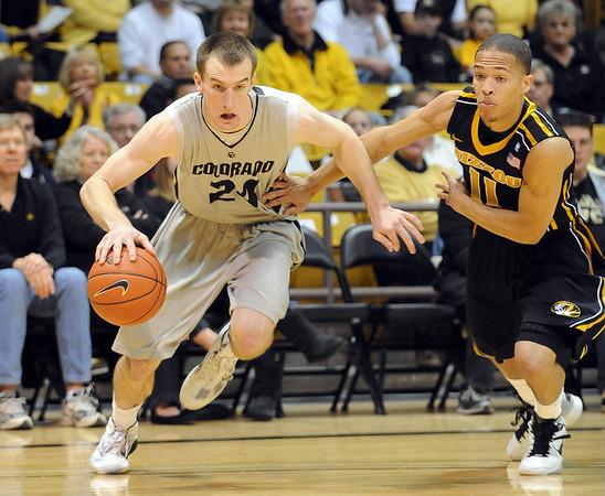 "Levi Knutson of Colorado drives around Michael Dixon of Missouri.<br /> For more photos of the game, go to  <a href=""http://www.dailycamera.com"">http://www.dailycamera.com</a>.<br /> Cliff Grassmick / January 8, 2011"