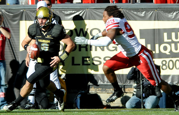 Tyler Hansen (9) tries to get away from a helmetless Barry Turner (99) during the University of Colorado game against Nebraska on Friday on Folsom Field in Boulder November 27, 2009.<br /> Photo by Cliff Grassmick / The Camera