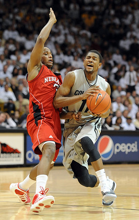 """Cory Higgins of CU drives past Brandon Richardson of Nebraska.<br /> For more photos of the game, go to  <a href=""""http://www.dailycamera.com"""">http://www.dailycamera.com</a>.<br /> Cliff Grassmick / March 5, 2011"""