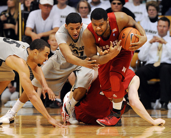 Marcus Relphorde, left, and Andre Roberson, both of Colorado, struggle with Lance Jeter of Nebraska during the first half of the March 5, 2011 game in Boulder.<br /> Cliff Grassmick / March 5, 2011