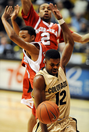Dwight Thorne of CU gets the ball knocked away by the Nebraska defender.<br /> Cliff Grassmick / January 27, 2010