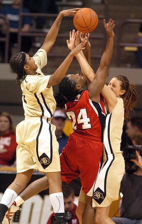 Brittany Spears, left, and Julie Seabrook, both of Colorado, foul Dominique Kelley of Nebraska during the first half of the January 30, 2010 game in Boulder.<br /> Cliff Grassmick / January 30, 2010