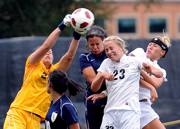 """UNC Keeper, Kirstin  Salminen, left, knocks the ball away from Anne Stuller  and Amy Barczuk, both of Colorado. JJ Wykstra of UNC is also defending.<br /> For more photos of the game, go to  <a href=""""http://www.dailycamera.com"""">http://www.dailycamera.com</a><br /> Cliff Grassmick / August 21, 2011"""