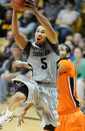 Marcus Relphorde of Colorado drives to the basket past Lathen Wallace of Oregon State in the second half of the December 4, 2010 game in Boulder.<br /> Cliff Grassmick / December 4, 2010