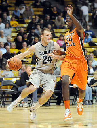 Levi Knutson (24) of Colorado, tries to drive around Omari Johnson of Oregon State during the first half of the December 4, 2010 game in Boulder.<br /> Cliff Grassmick / December 4, 2010