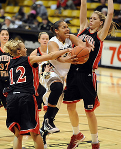 Bianca Smith of Colorado drives between Jadie Parsons (12) and Challis Pascucci of Southern Utah.  Cliff Grassmick / December 19, 2009
