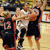 Bianca Smith of Colorado drives between Jadie Parsons (12) and Challis Pascucci of Southern Utah.<br /> <br /> Cliff Grassmick / December 19, 2009