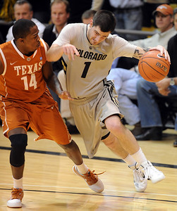 Nate Tomlinson of CU collides with J'covan Brown of Texas. For more photos of the game, go to www.dailycamera.com Cliff Grassmick / February 26, 2011