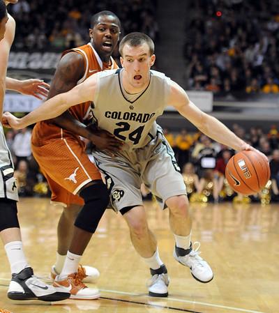 "Levi Knutson of Colorado scrapes off  J'covan Brown of Texas.<br /> For more photos of the game, go to  <a href=""http://www.dailycamera.com"">http://www.dailycamera.com</a><br /> Cliff Grassmick / February 26, 2011"