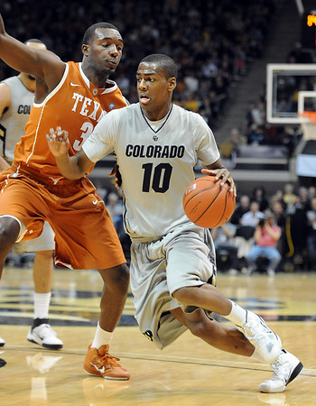 "Alec Burks of Colorado drives around Jordan Hamilton of Texas.<br /> For more photos of the game, go to  <a href=""http://www.dailycamera.com"">http://www.dailycamera.com</a><br /> Cliff Grassmick / February 26, 2011"