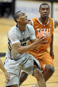 Alec Burks of CU drives past Jordan Hamilton of Texas. For more photos of the game, go to www.dailycamera.com Cliff Grassmick / February 26, 2011