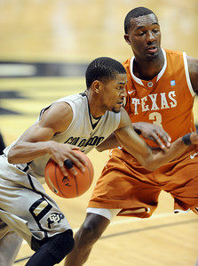 Cory Higgins of CU drives past Jordan Hamilton of Texas. For more photos of the game, go to www.dailycamera.com Cliff Grassmick / February 26, 2011