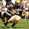 University of Colorado tailback Rodney Stewart tries to break a tackle from Texas Tech safety Cody Davis during the football game against Texas Tech on Saturday, Oct. 23, at Folsom Field.<br /> Jeremy Papasso/ Camera