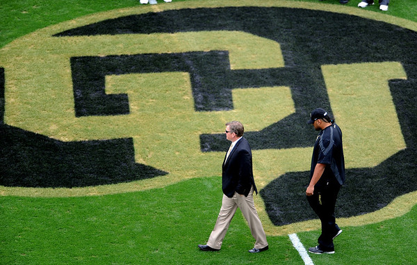 """University of Colorado  football coach, Dan Hawkins, walks past the buffalo at midfield before the Texas Tech game at Folsom Field.<br /> For more photos of the game, go to  <a href=""""http://www.dailycamera.com"""">http://www.dailycamera.com</a><br /> Cliff Grassmick / October 23, 2010"""