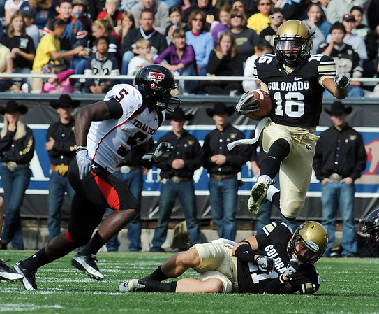 "Will Jefferson of CU jumps over Scotty McKnight to pick up yards against Texas Tech.<br /> For more photos of the game, go to  <a href=""http://www.dailycamera.com"">http://www.dailycamera.com</a>.<br /> Cliff Grassmick / October 23, 2010"