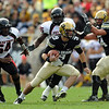 University of Colorado quarterback, Tyler Hansen looks for room to run as Dartwan Bush, left, and Pearlie Graves, both of Texas Tech are in pursuit in the first half of the October 23, 2010 game in Boulder.<br /> Cliff Grassmick / October 23, 2010