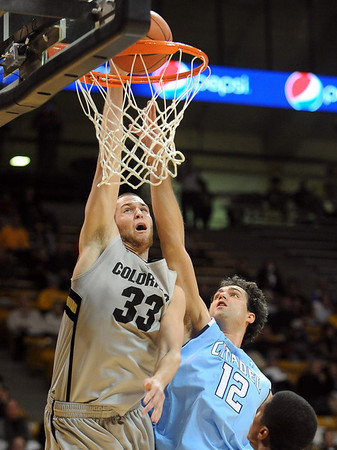 Austin Dufault (33) of Colorado, dunks on Mike Dejworek of The Citadel during the first half of the December 17, 2010 game in Boulder.<br /> Cliff Grassmick / December 17, 2010