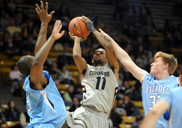Cory Higgins of Colorado, shoots between Bryan Streeter, left, and Daniel Eykyn of The Citadel during the first half of the December 17, 2010 game in Boulder.<br /> Cliff Grassmick / December 17, 2010