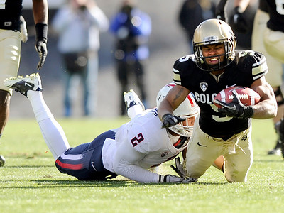 University of Colorado's Rodney Stewart is tackled by Arizona's Marquis Flowers during a game against the University of Arizona on Saturday, Nov. 12, at Folsom Field on the CU campus in Boulder. For more photos of the game go to www.dailycamera.com Jeremy Papasso/ Camera