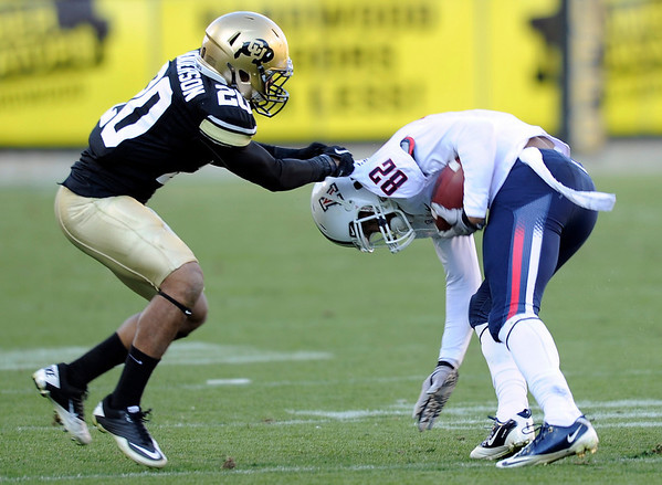 "University of Colorado's Greg Henderson tries to make a tackle on Arizona's Juron Criner during a game against the University of Arizona on Saturday, Nov. 12, at Folsom Field on the CU campus in Boulder. CU won the game 48-29. For more photos of the game go to  <a href=""http://www.dailycamera.com"">http://www.dailycamera.com</a><br /> Jeremy Papasso/ Camera"