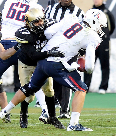 "University of Colorado's Josh Hartigan sacks Arizona quarterback Nick Foles during a game against the University of Arizona on Saturday, Nov. 12, at Folsom Field on the CU campus in Boulder. CU won the game 48-29. For more photos of the game go to  <a href=""http://www.dailycamera.com"">http://www.dailycamera.com</a><br /> Jeremy Papasso/ Camera"