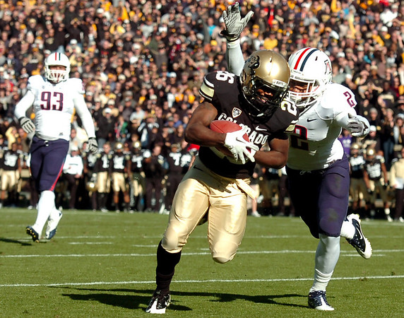 "University of Colorado's Tony Jones rushes in for a touchdown past Arizona's Marquis Flowers during a game against the University of Arizona on Saturday, Nov. 12, at Folsom Field on the CU campus in Boulder. CU won the game 48-29. For more photos of the game go to  <a href=""http://www.dailycamera.com"">http://www.dailycamera.com</a><br /> Jeremy Papasso/ Camera"