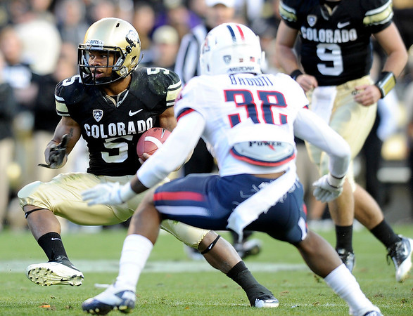 "University of Colorado's Rodney Stewart rushes the ball past Arizona's Lyle Brown during a game against the University of Arizona on Saturday, Nov. 12, at Folsom Field on the CU campus in Boulder. CU won the game 48-29. For more photos of the game go to  <a href=""http://www.dailycamera.com"">http://www.dailycamera.com</a><br /> Jeremy Papasso/ Camera"