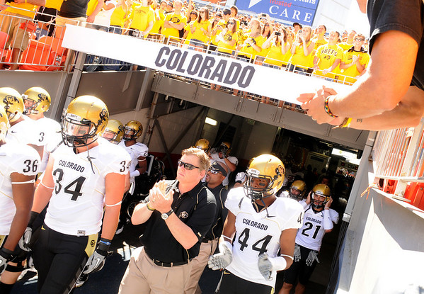 Jim Mahnke, 46, of Phoenix, right, claps for the University of Colorado football team as they enter the stadium before the game against Colorado State University on Saturday, Sept. 4, at Invesco Field in Denver. CU player Ryan Deehan, left, head coach Dan Hawkins and Nick Kasa, right, come out of the tunnel and enter the field.<br /> Photo by JEREMY PAPASSO