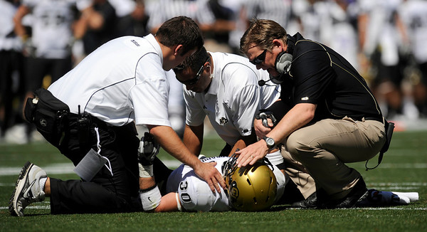 University of Colorado football player Parker Orms is attended to by coach Dan Hawkins and two trainers after being injured in a first quarter punt by CU at the game against Colorado State University on Saturday, Sept. 4, at Invesco Field in Denver.<br /> Photo by JEREMY PAPASSO