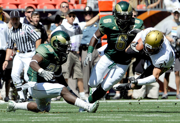 Colorado's Scotty McKnight (right) is tackled by Colorado State's Ivory Herd (left) and Chris Nwoke (middle) during their football game  in Denver, Colorado September 4, 2010.  CAMERA/Mark Leffingwell