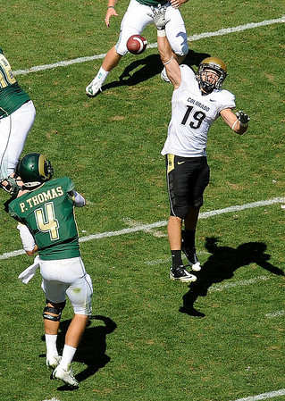 University of Colorado defenseman Travis Sandersfeld attempts to block a pass from CSU quarterback Pete Thomas during the fourth quarter of the game against Colorado State University on Saturday, Sept. 4, at Invesco Field in Denver.<br /> Photo by JEREMY PAPASSO