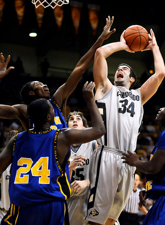 Colorado's Casey Crawford (right) powers through Coppin State's Sam Coleman (back left) and Kareem Brown (front left) for a basket during their basketball game at the University of Colorado in Boulder, Colorado November 16, 2009. CAMERA/Mark Leffingwell