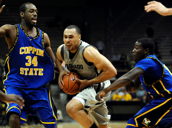 Colorado's Marcus Relphorde (middle) plows past Coppin State's Branden Doughty (left) Kareem Brown (right) during their basketball game at the University of Colorado in Boulder, Colorado November 16, 2009. CAMERA/Mark Leffingwell