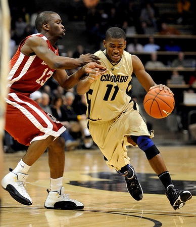 Colorado's Cory Higgins (right) drives in for a shot while being guarded by Oklahoma's Willie Warren (left) during their basketball game at the University of Colorado in Boulder, Colorado February 17, 2010.  CAMERA/Mark Leffingwell