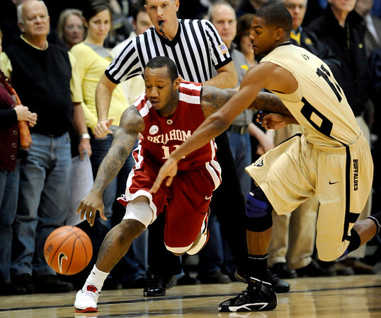 Colorado's Cory Higgins (right) tries to knock the ball from the hands of Oklahoma's Tommy Mason-Griffin (left) during their basketball game at the University of Colorado in Boulder, Colorado February 17, 2010.  CAMERA/Mark Leffingwell