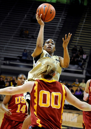 University of Colorado freshman Brittany Wilson takes a shot over Trojan defenders during the 2011  WNIT  game against Southern California on Sunday, March 27, at the Coors Event Center on the CU campus in Boulder.<br />  Jeremy Papasso/ Camera