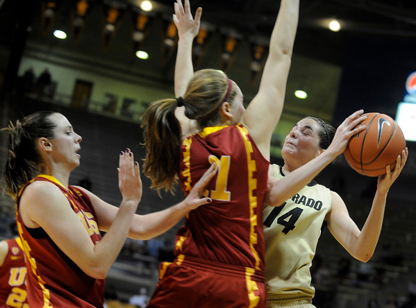 University of Colorado sophomore Meagan Malcolm-Peck tries to drives past Trojan defenders during the 2011  WNIT  game against Southern California on Sunday, March 27, at the Coors Event Center on the CU campus in Boulder.<br /> The Buffs lost the game 87-70.<br />  Jeremy Papasso/ Camera