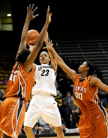 Colorado's Chucky Jeffery (center) shoots between the arms of Texas' Ashley Gayle (left) and Earnesia Williams during their basketball game at University of Colorado in Boulder, Colorado February 10, 2010.  CAMERA/Mark Leffingwell