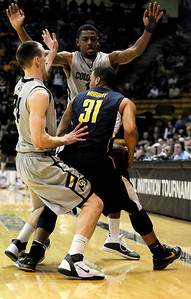 Levi Knutson, left, and Alec Burks play defense against Emerson Murray of the University of California at the Coors Event Center in Boulder on Friday, March 18,2011. For more photos go to www.dailycamera.com (Phil McMichael/ Camera)