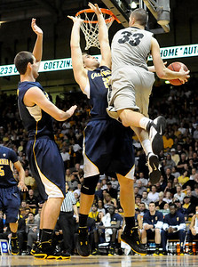 Austin Dufault passes the ball in the game versus the University of California at the Coors Event Center in Boulder on Friday, March 18,2011. For more photos go to www.dailycamera.com (Phil McMichael/ Camera)