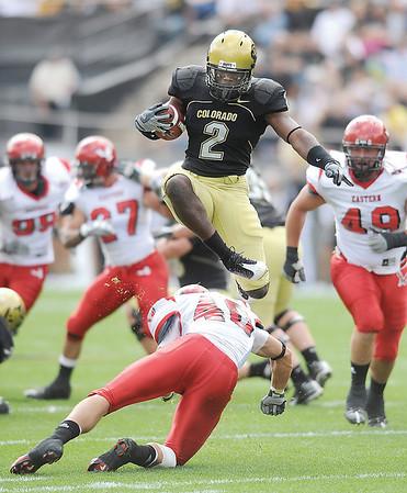 Darrell Scott of CU jumps over the tackle attempt of Matt Johnson of EWU on Saturday.<br /> Cliff Grassmick / Daily Camera, SEPTEMBER 6, 2008