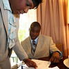 DSCOTT307.JPG (NYT86) ANAHEIM,. Calif. -- Feb. 6, 2008 -- FBC-RECRUIT-3 -- Darrell Scott, a high school senior, with his mother Alexis Scott, signs his college commitment papers at the Portofino Inn & Suites in Anaheim, Calif., on Wednesday, Feb. 6, 2008. Scott, considered the nation's top high school running back is viewed as a recruiting prize. At 6 feet 2 inches and 215 pounds, he has been clocked at 4.4 seconds for the 40-yard dash. He rushed for 2,443 yards and 33 touchdowns on just 275 carries this season. His decision gives University of Colorado football coach Dan Hawkins a signature recruit to continue building around. In two seasons at Colorado, Hawkins has worked to overcome scars left by past off-field scandals. (Marissa Roth/The New York Times)