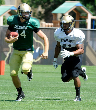 """Quarterback John Schrock, 14, scrambles away from Terrel Smith, 41, during the University of Colorado Football team scrimmage on Saturday August 13, 2011.<br /> For more photos and video interviews from the scrimmage go to  <a href=""""http://www.buffzone.com"""">http://www.buffzone.com</a> and dailycamera.com<br /> Photo by Paul Aiken  August 13,  2011."""