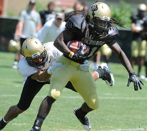 "DD. Goodson, 21, escapes from K.T. Tu'umalo 42, during the University of Colorado Football team scrimmage on Saturday August 13, 2011.<br /> For more photos and video interviews from the scrimmage go to  <a href=""http://www.buffzone.com"">http://www.buffzone.com</a> and dailycamera.com<br /> Photo by Paul Aiken  August 13,  2011."