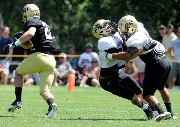 "Terrel Smith, 41, and Will Harlos, 28, smash together as Nelson Spruce 22, escapes during the University of Colorado Football team scrimmage on Saturday August 13, 2011.<br /> For more photos and video interviews from the scrimmage go to  <a href=""http://www.buffzone.com"">http://www.buffzone.com</a> and dailycamera.com<br /> Photo by Paul Aiken  August 13,  2011."